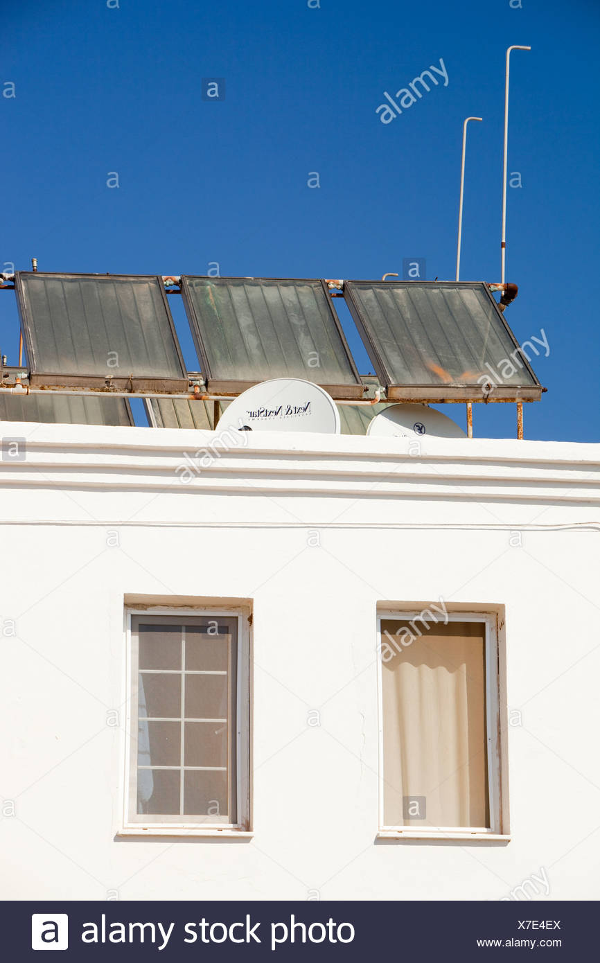 Solar water heating panels on the roof of a launderette in Teos, Turkey - Stock Image