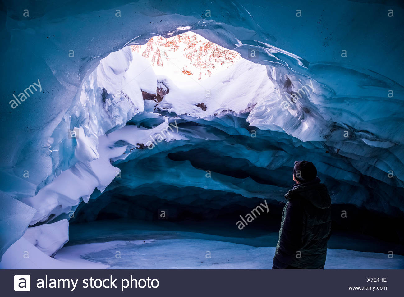 A man looks out an opening in the ceiling of an ice cave within Augustana Glacier in the winter, Alaska Range, Interior Alaska, USA - Stock Image