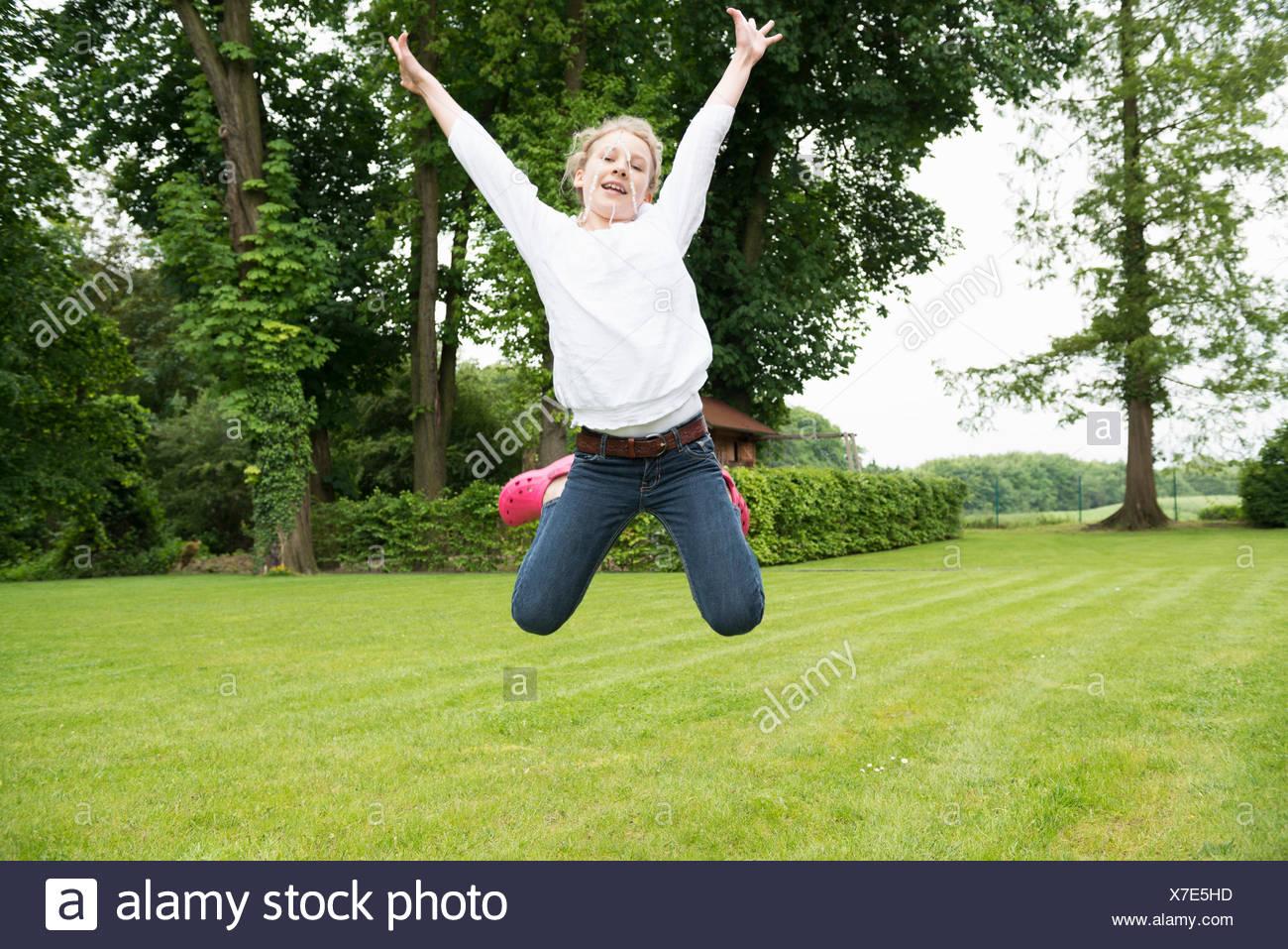 Girl jumping in garden - Stock Image
