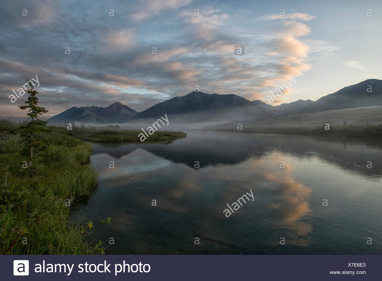 Landscape images from the Wind River, a tributary of the Main Peel River. Mackenzie Mountains reflected in the calm waters of the Wind River. Stock Photo