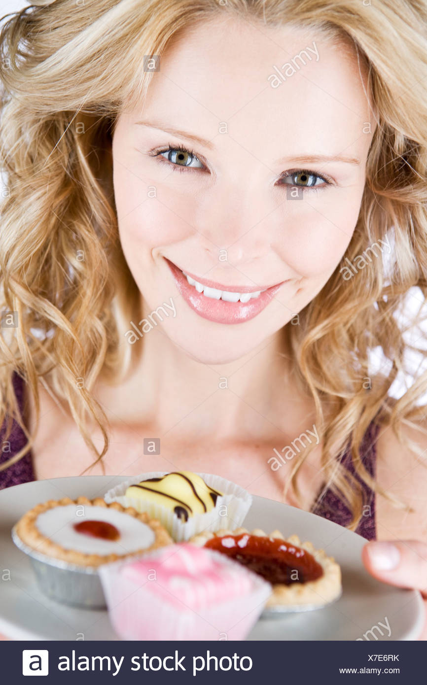 A portrait of a young blond woman holding a plate of assorted cakes - Stock Image