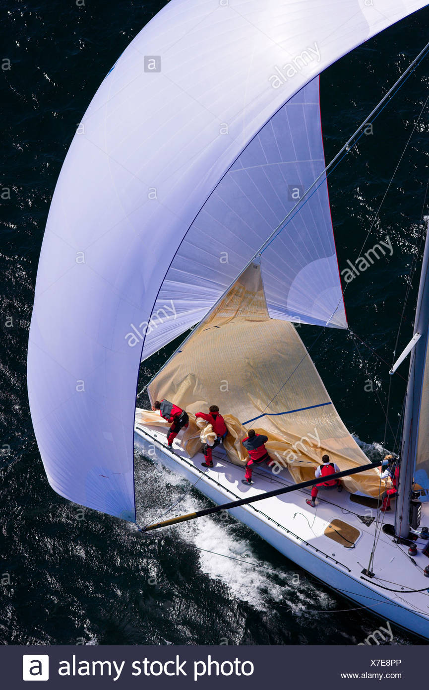 Crew taking down the head sail while sailing downwind under spinnaker in the 2006 12 Metre North American Championships, Newport - Stock Image