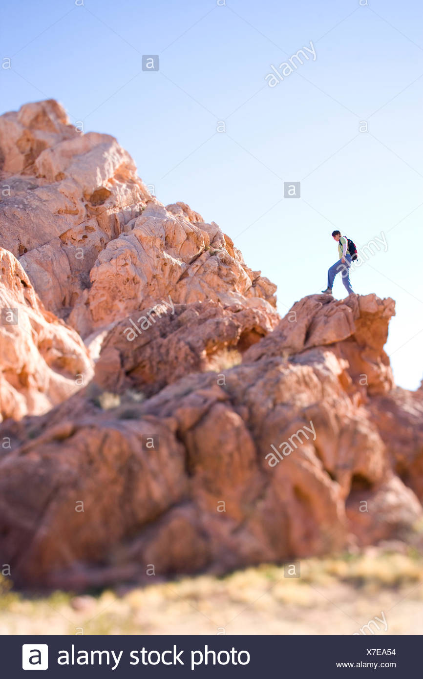 Woman hiker standing atop grouping of red rocks. - Stock Image