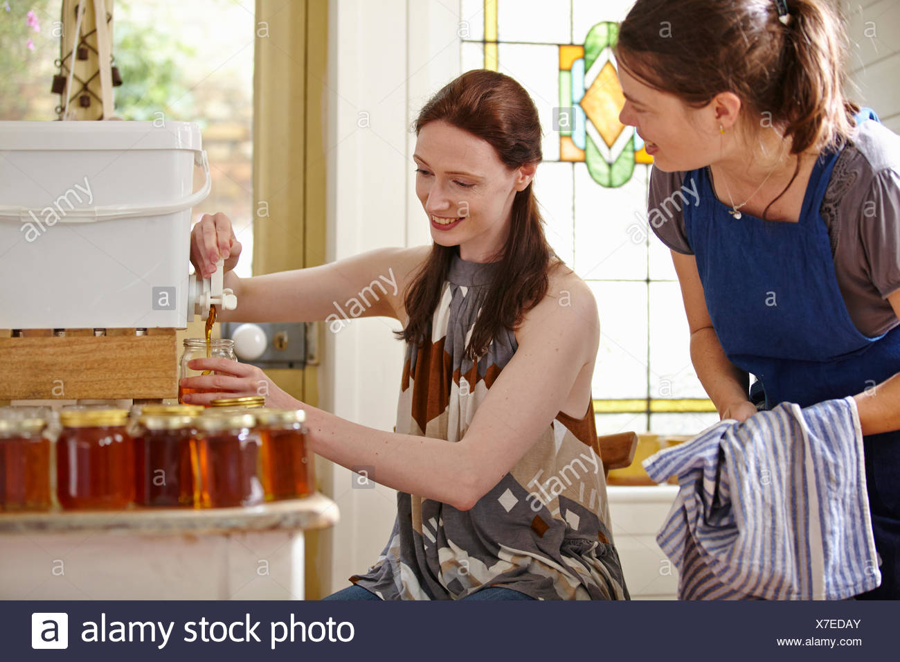 Female beekeepers in kitchen, bottling filtered honey from beehive - Stock Image