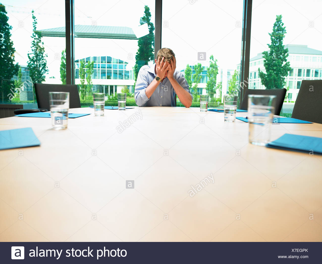 Business man in a empty conference room - Stock Image