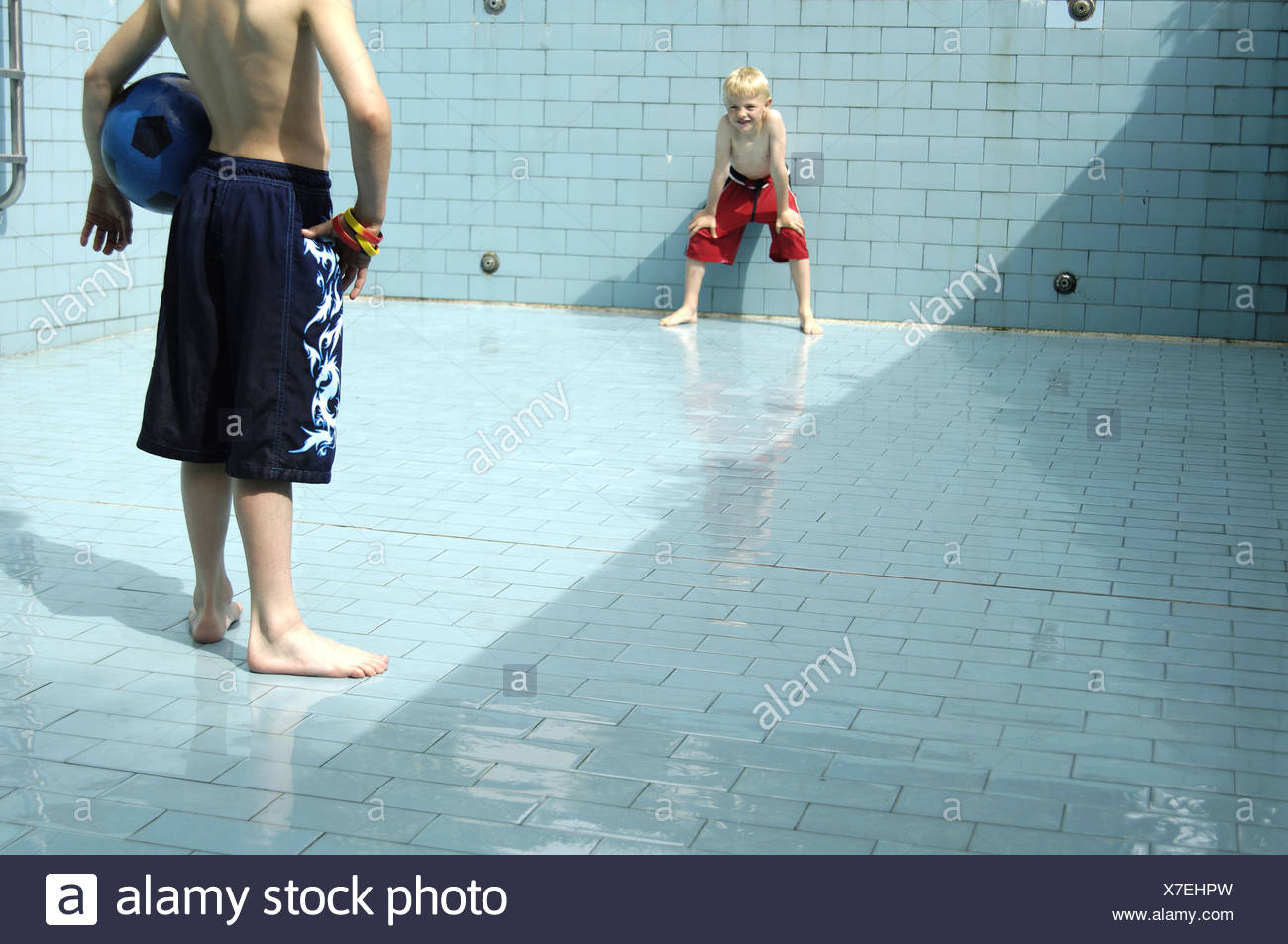 Pool empty children soccer games detail series people boys bath-clothing pools basin-ground tiles ball ball-game activity fun - Stock Image