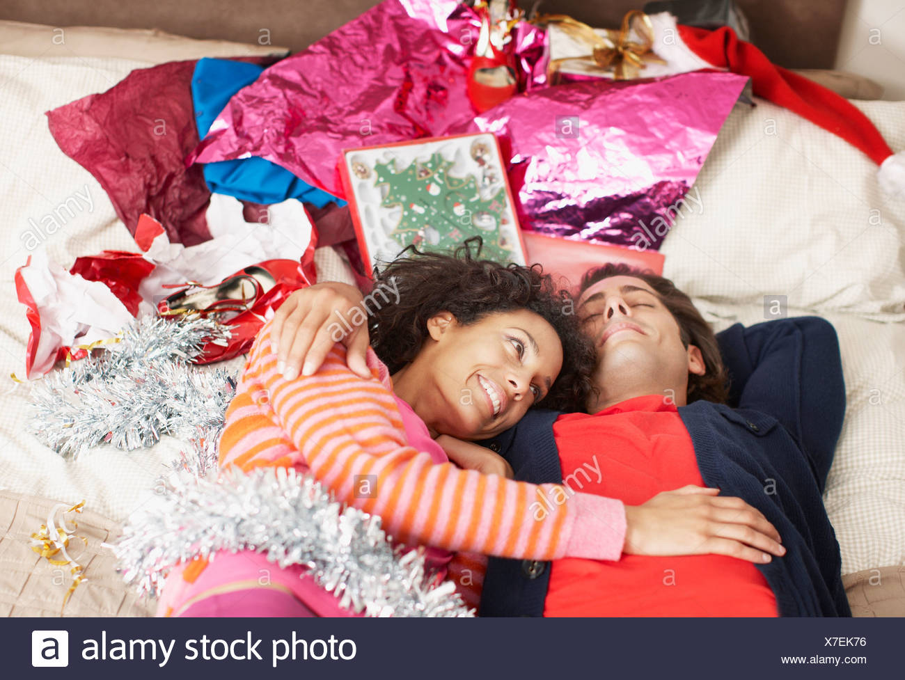 Couple hugging on bed with Christmas gifts - Stock Image