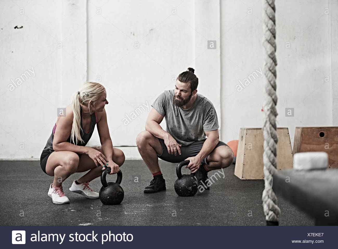 Couple with kettlebells in cross training gym - Stock Image