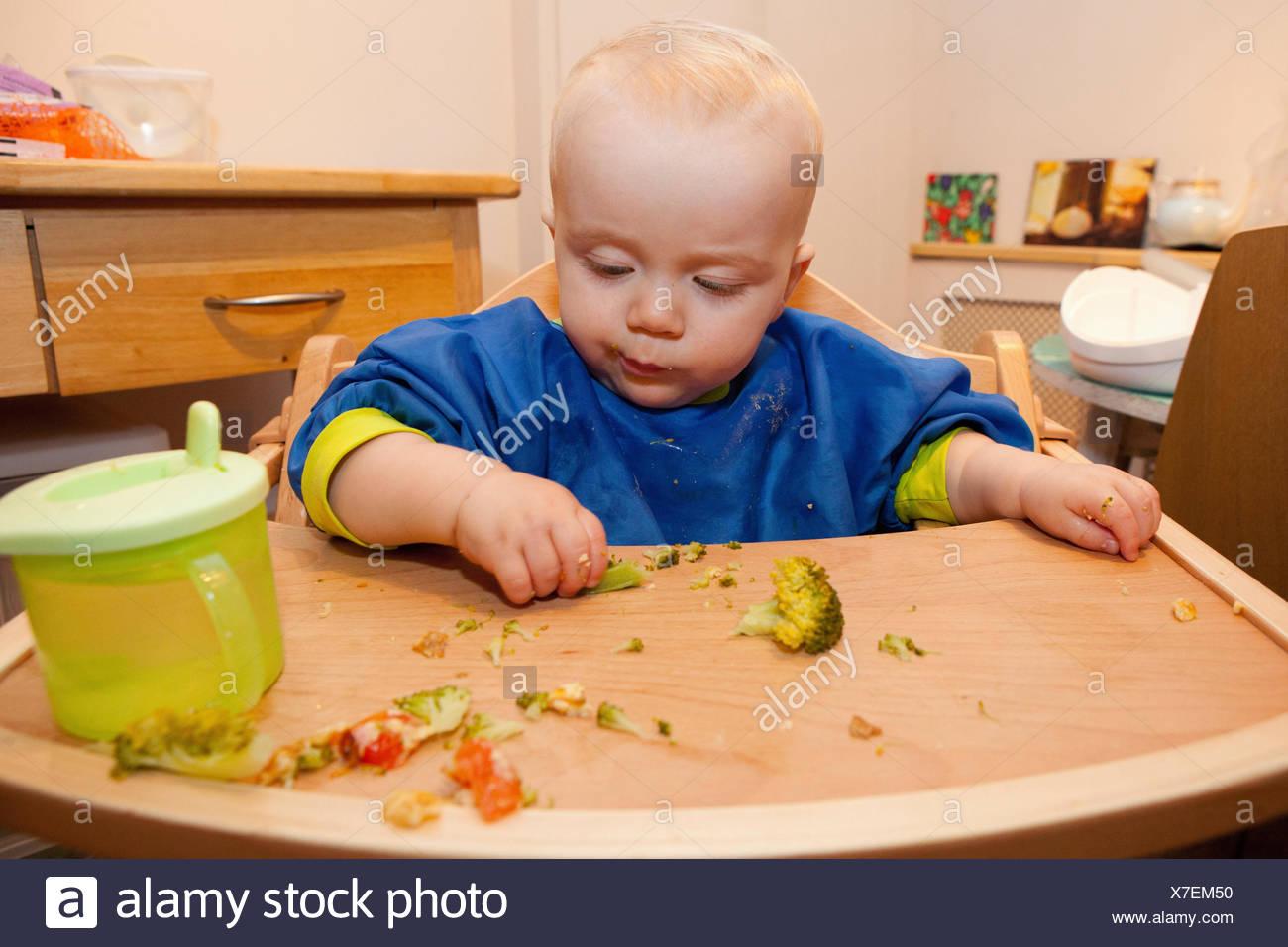 Baby feeding himself - Stock Image