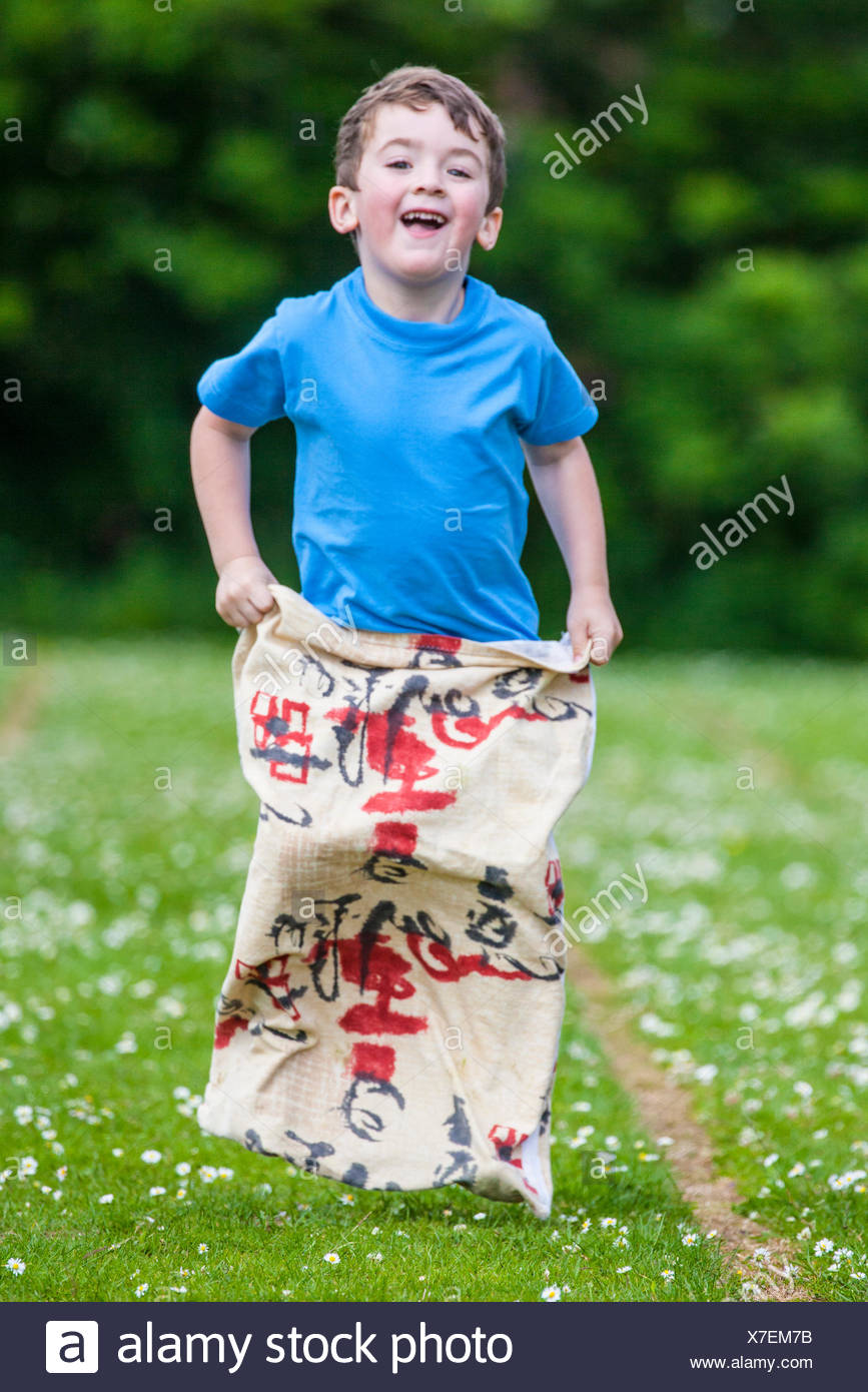 young boy, 4, competing in sack race in pre-school sports day - Stock Image