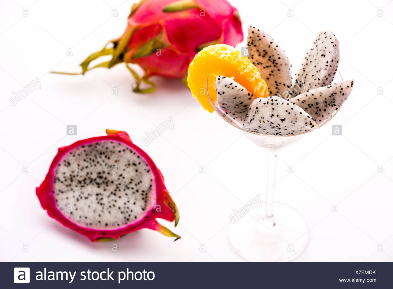 White pulp of half a pitaya cut into wedges and presented in a glass. The decorative mandarine slice is also complementing the pitaya's flavor. - Stock Image