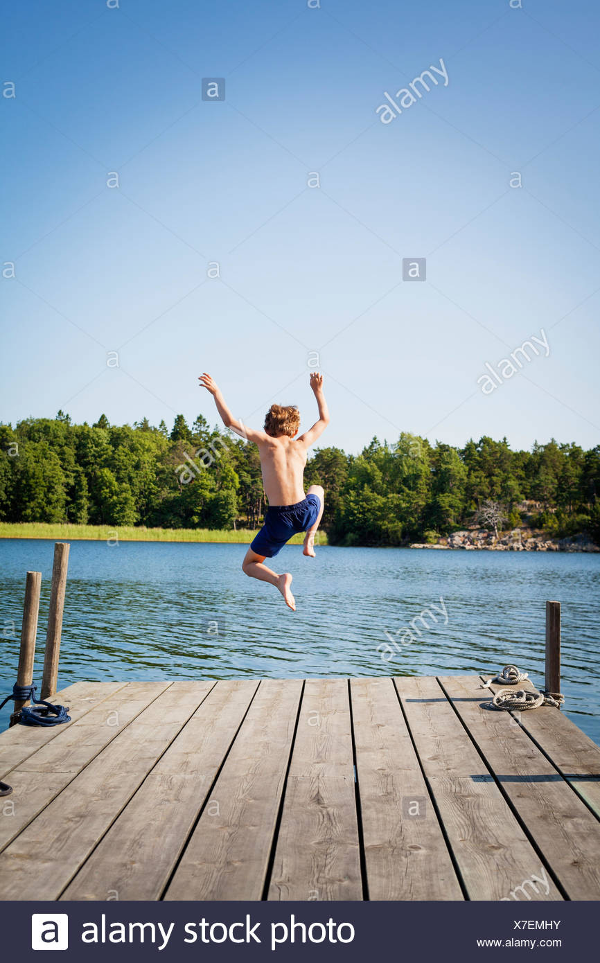 Sweden, Uppland, Runmaro, Barrskar, Rear view of boy (6-7) diving into water from jetty - Stock Image
