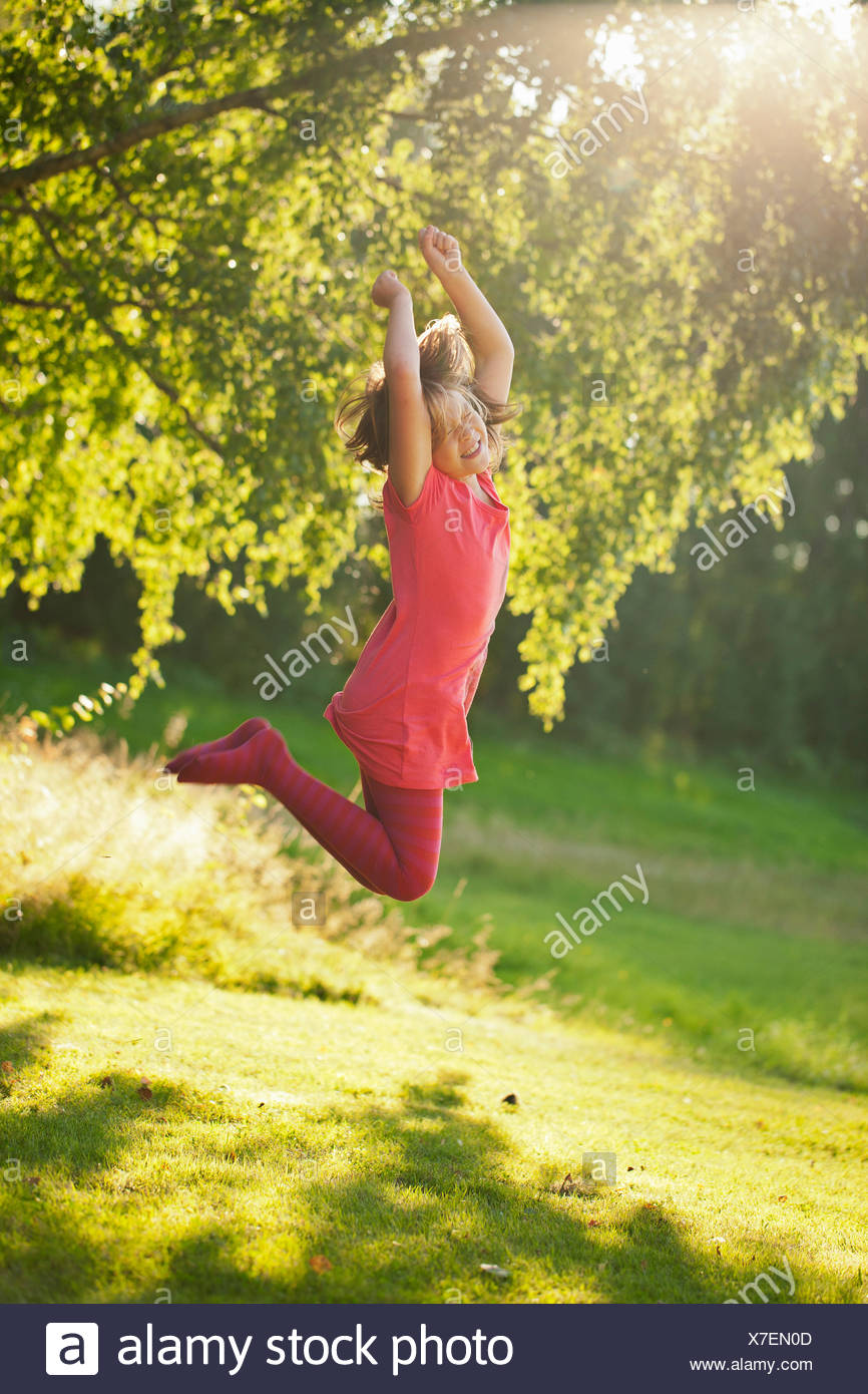 Girl (10-11) jumping in park - Stock Image