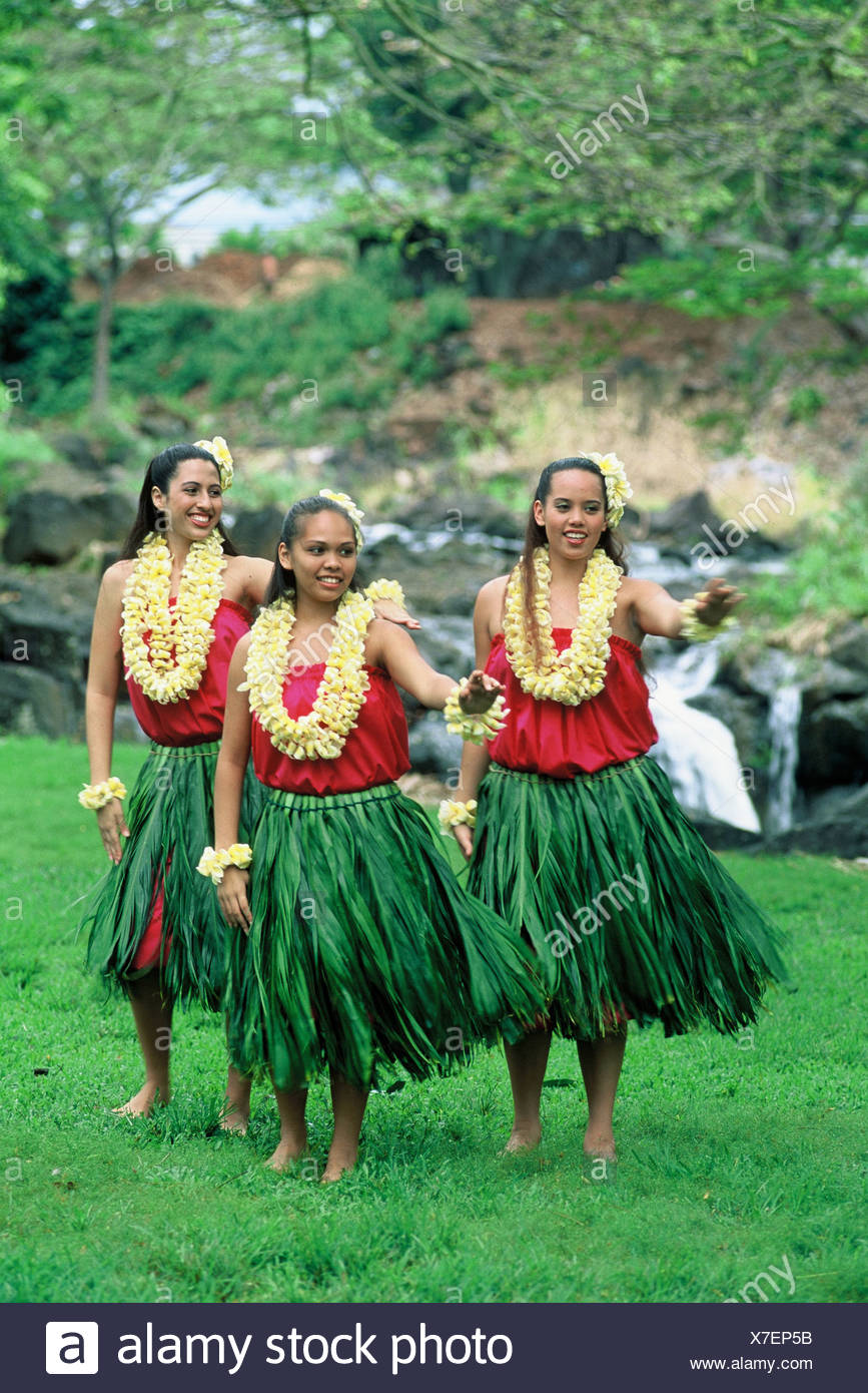 Three hula dancers near Waterfall in ti leaf skirts and yellow plumeria leis - Stock Image