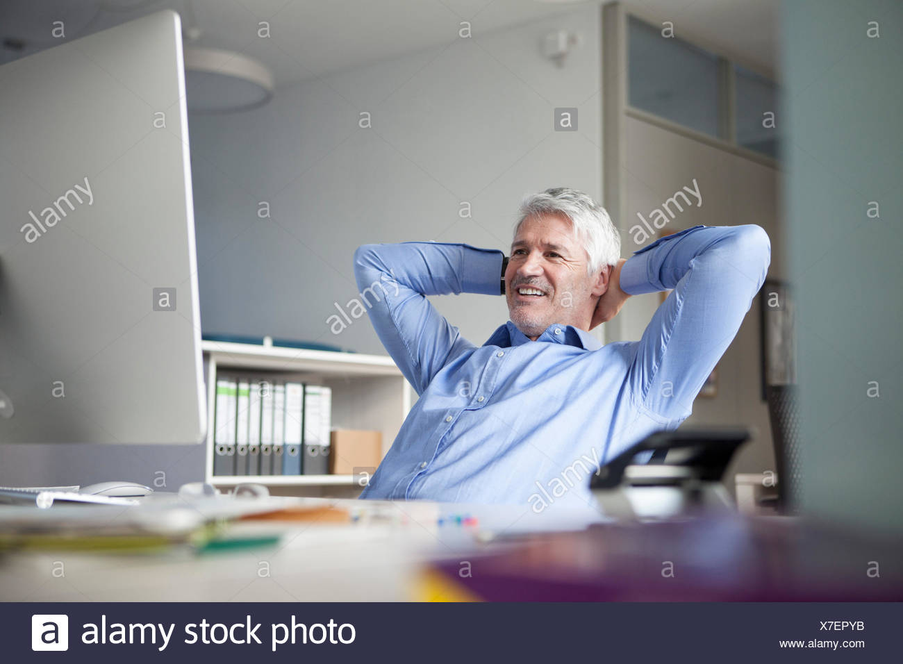 Businessman sitting at desk, hands behind head - Stock Image