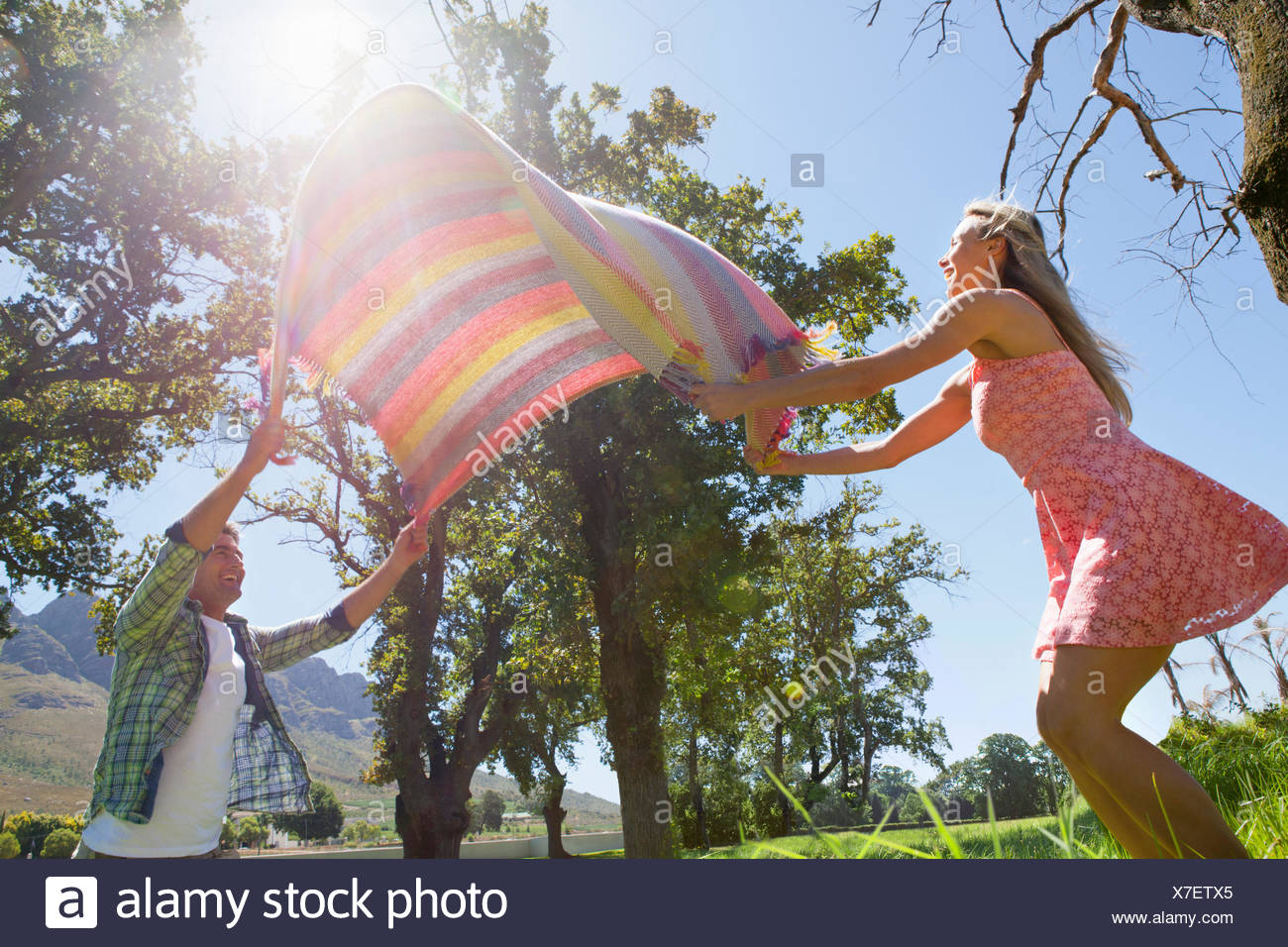 Couple laying picnic blanket in field - Stock Image