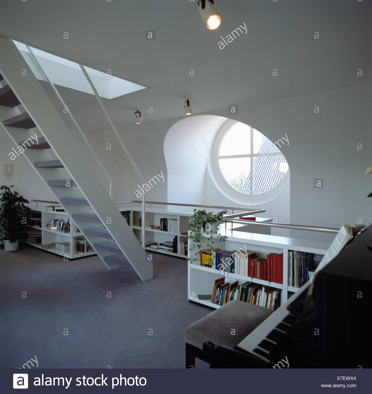 Circular Window Above Low Bookshelves In Modern White Loft Conversion  Living Room With Piano And Staircase