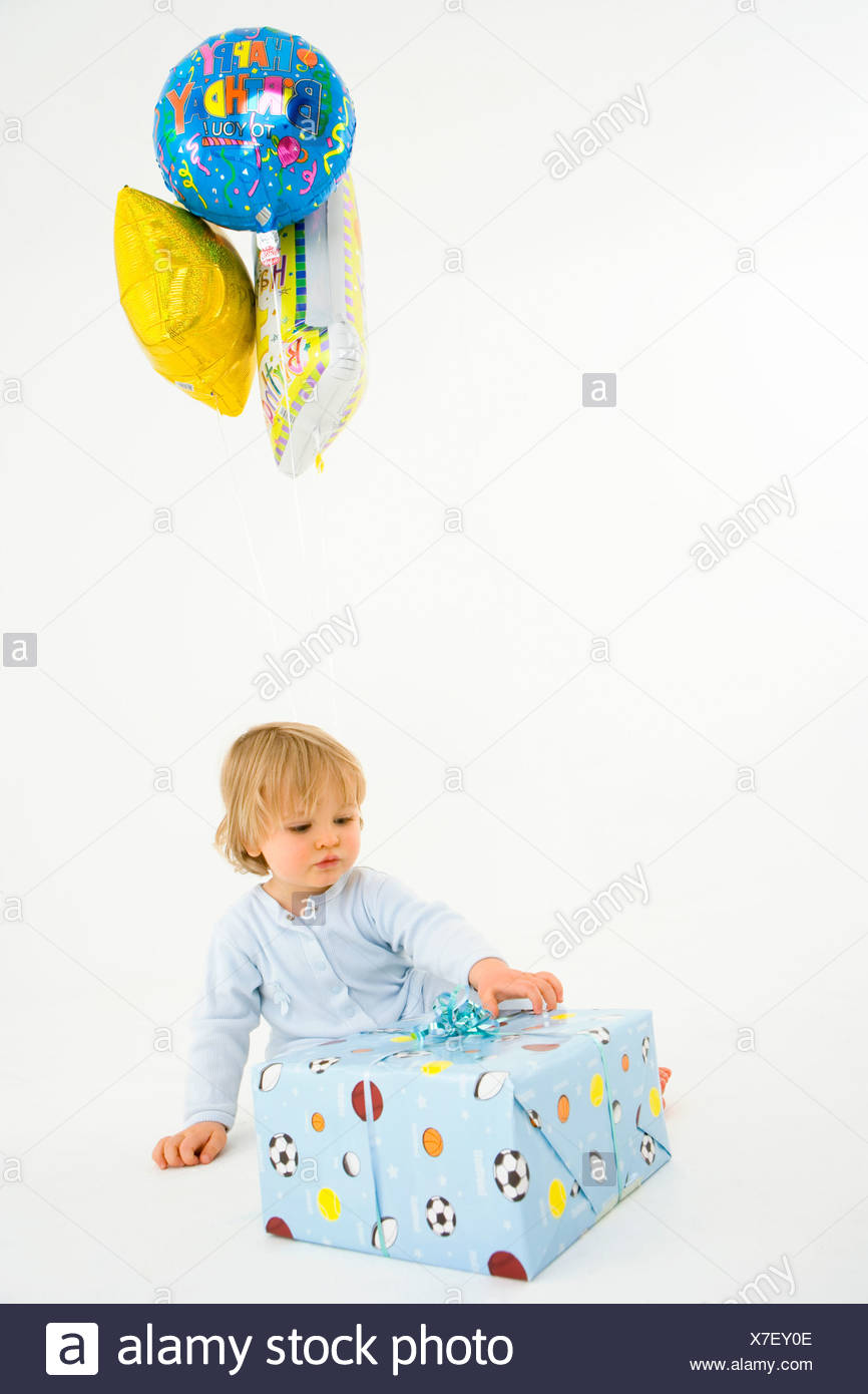 Baby boy 6-9 months with balloons and present - Stock Image