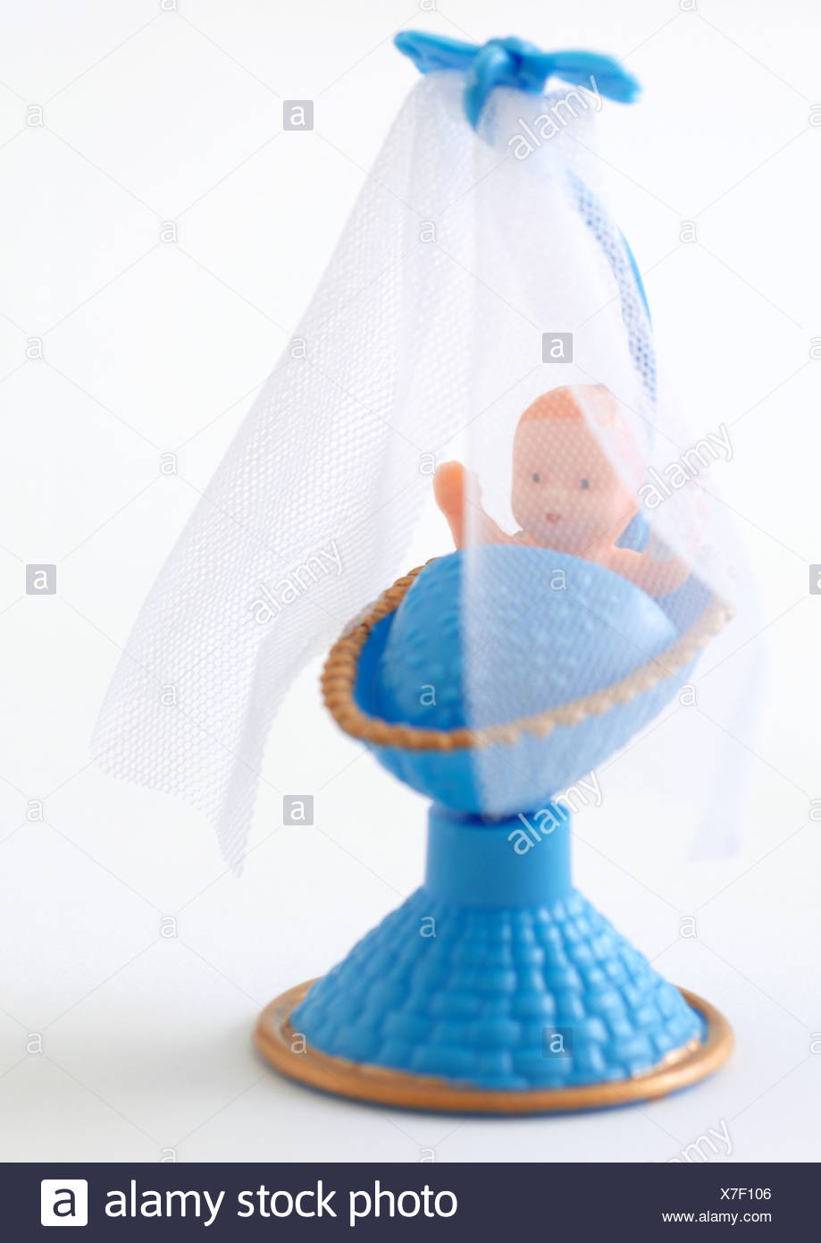 Plastic baby in blue crib - Stock Image