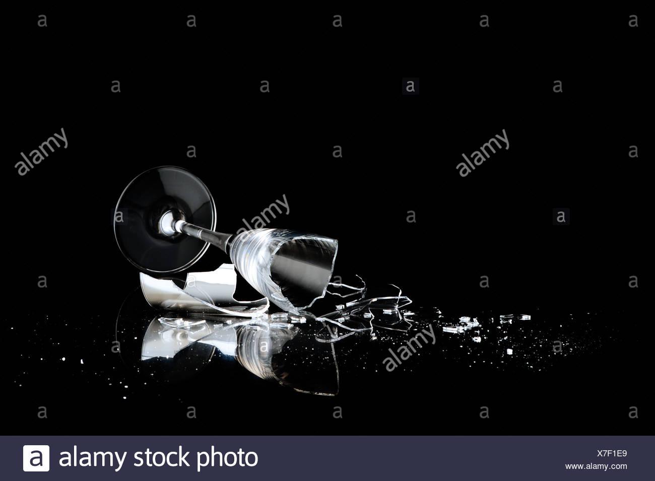 elegant wine glass broken on a dark background - Stock Image