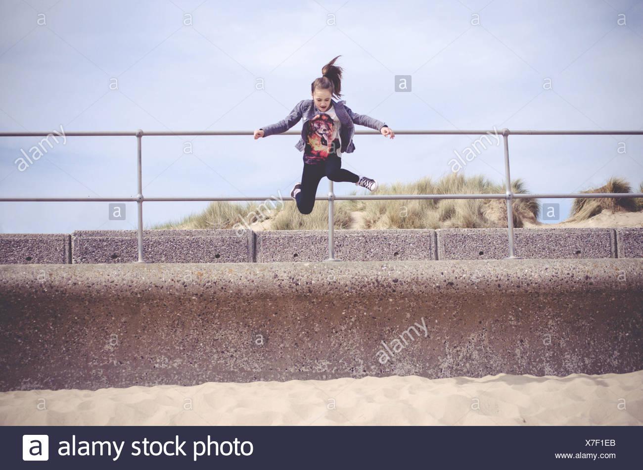 Girl jumping onto beach - Stock Image