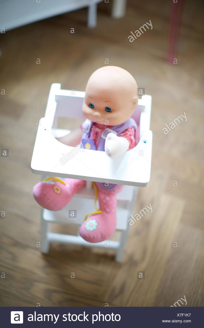 doll in baby chair. toy, children's room, wooden floor, childhood. Stock Photo