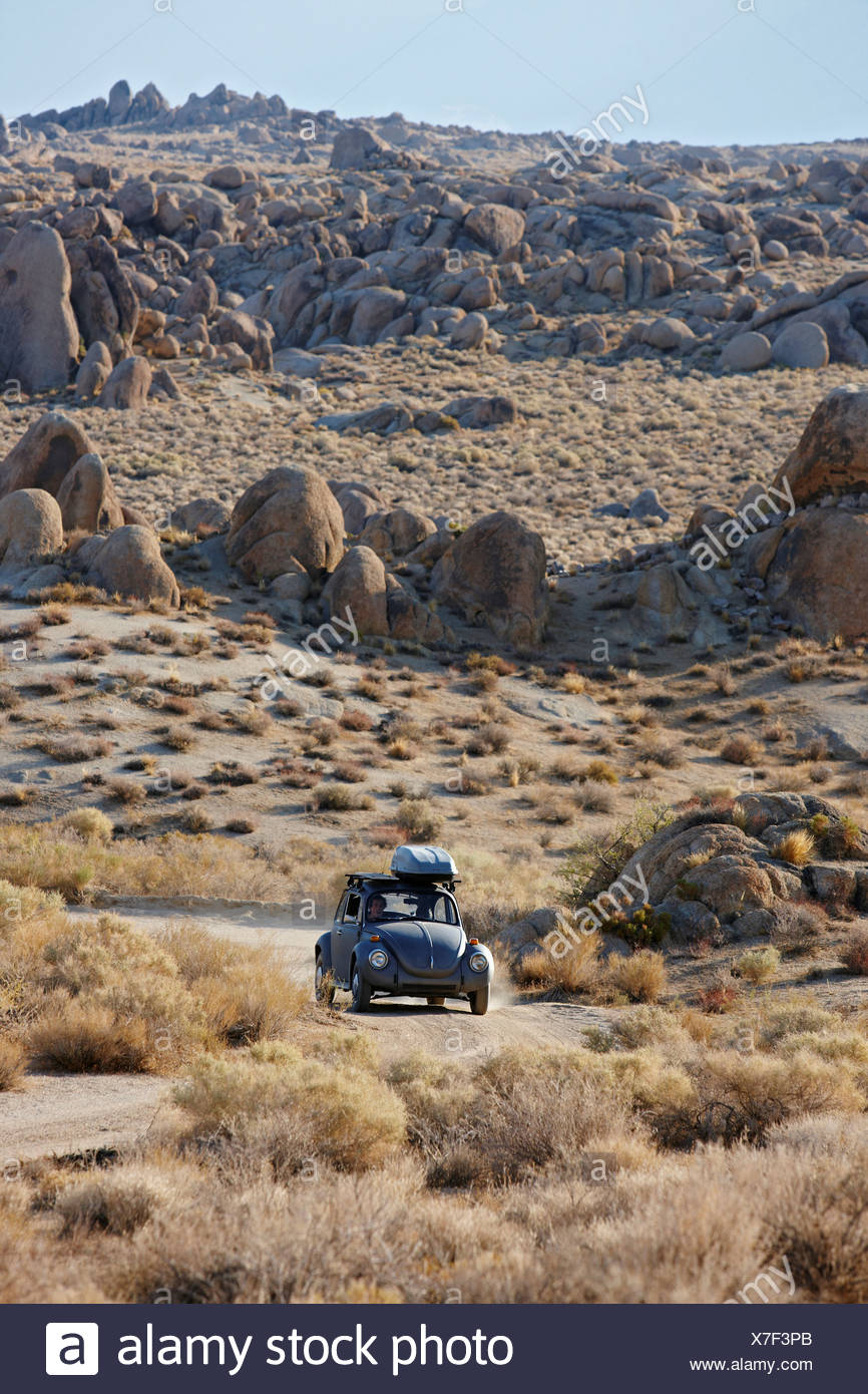 A vintage Volkswagen Beetle plies dirt road amid boulders in California's Alabama Hills below Mount Whitney in Sierra Nevada - Stock Image