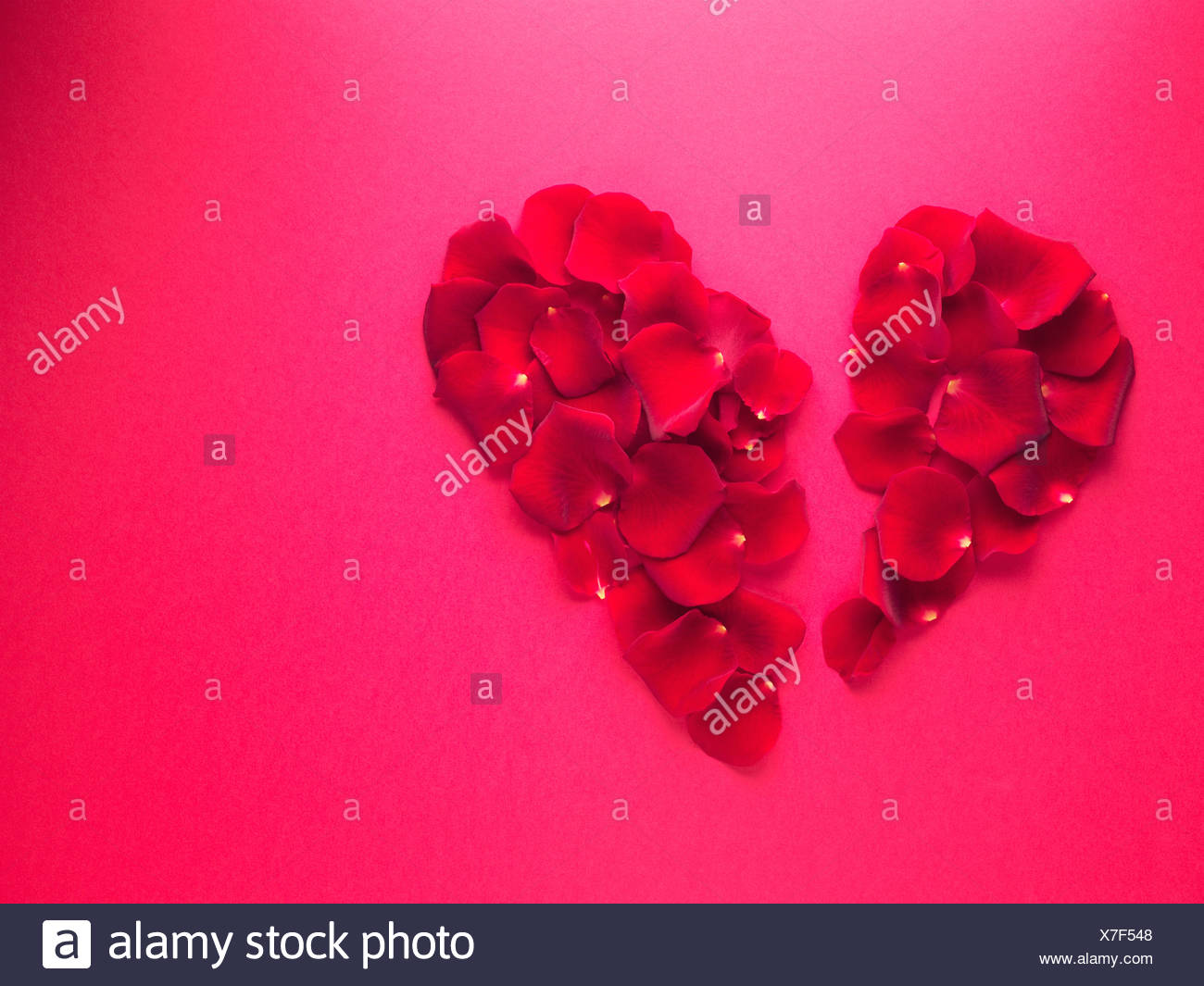 Red rose petals forming broken heart-shape - Stock Image