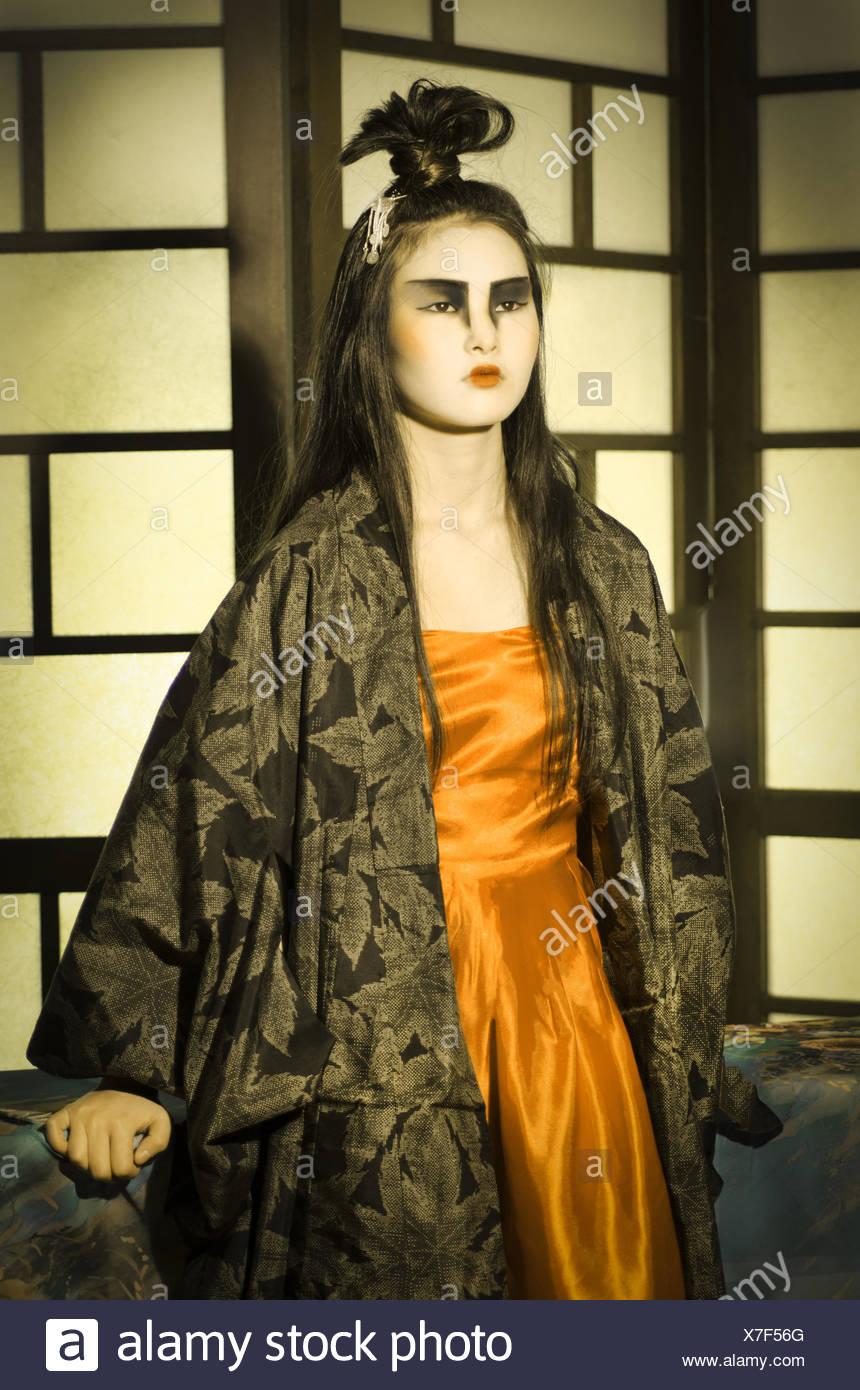 Beautiful young Japanese woman wearing orange dress and kimono. - Stock Image