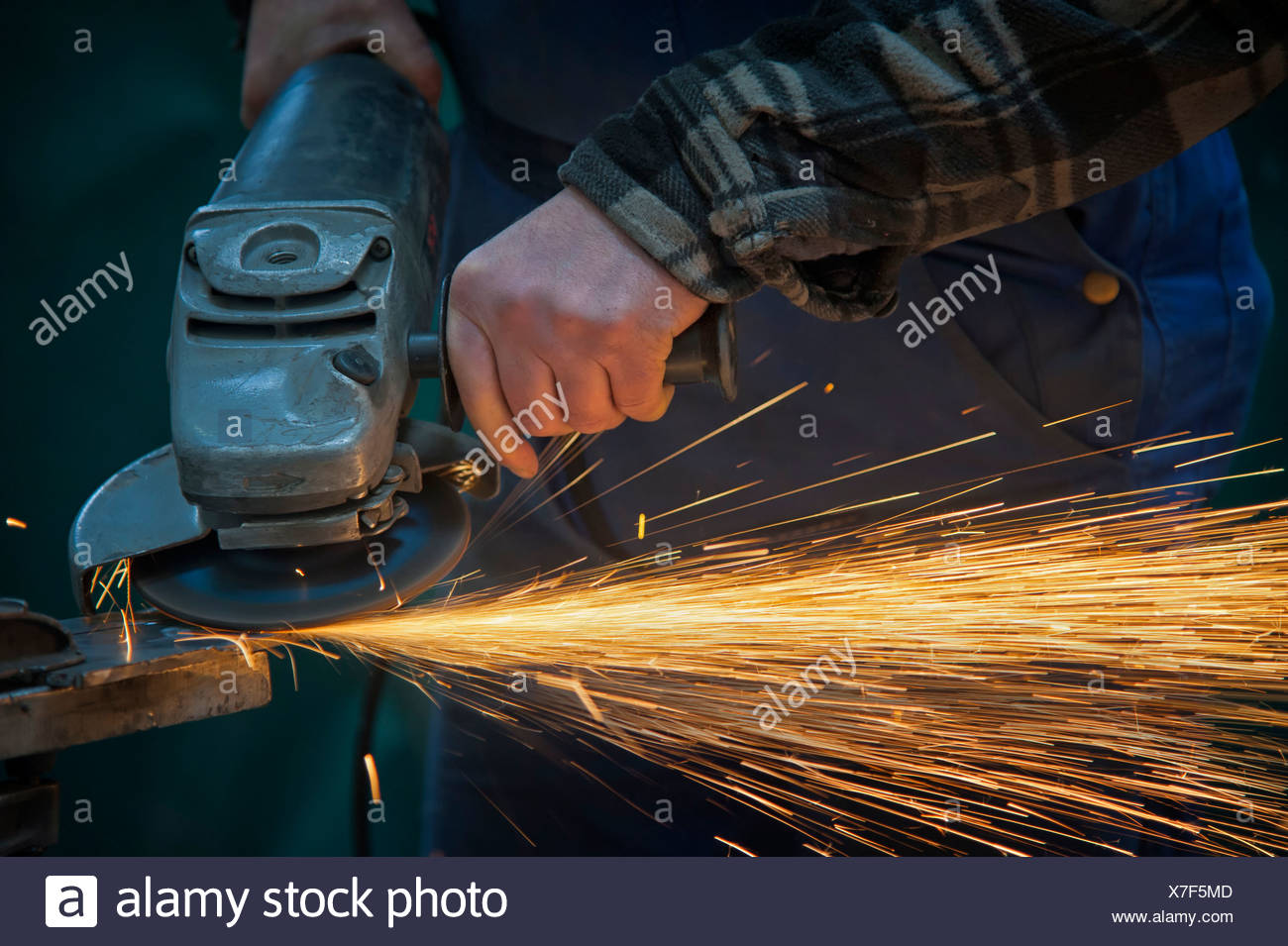 Hands of a worker using an angle grinder - Stock Image