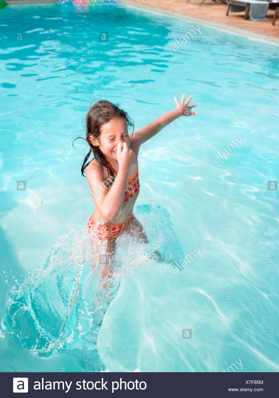 Girl jumping in swimming pool. Stock Photo