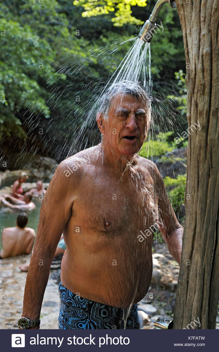 Tourist taking a shower at the hot springs, near the Hacienda Guachipelin, near Liberia, Guanacaste province, Costa Rica - Stock Image