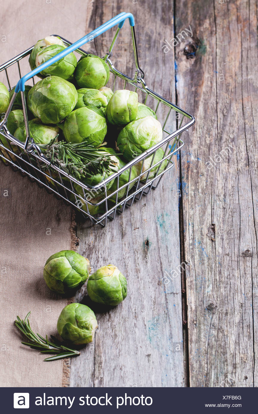 Food basket of brussels sprouts and rosemary on old wooden table. - Stock Image