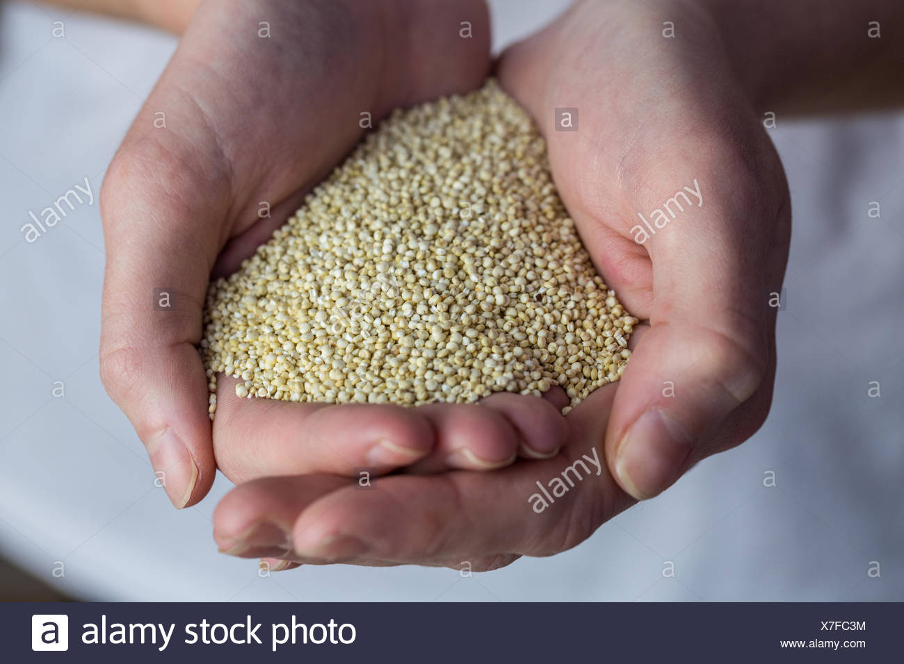 Woman showing handful of sesame seed - Stock Image