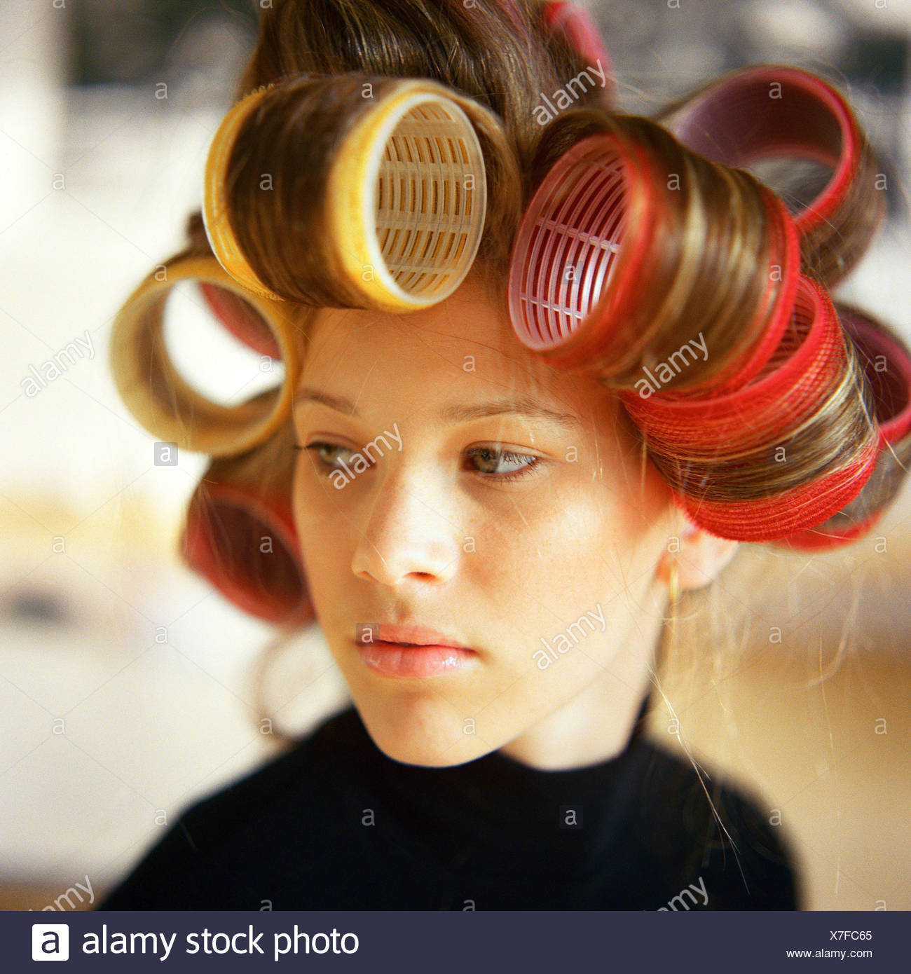 Young woman with rollers in hair - Stock Image