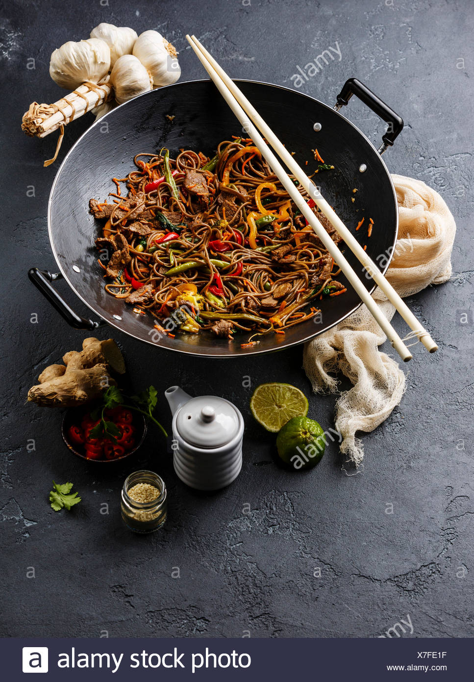 Asian fast food Stir fry noodles soba with beef and vegetables in wok pan on dark stone background Stock Photo