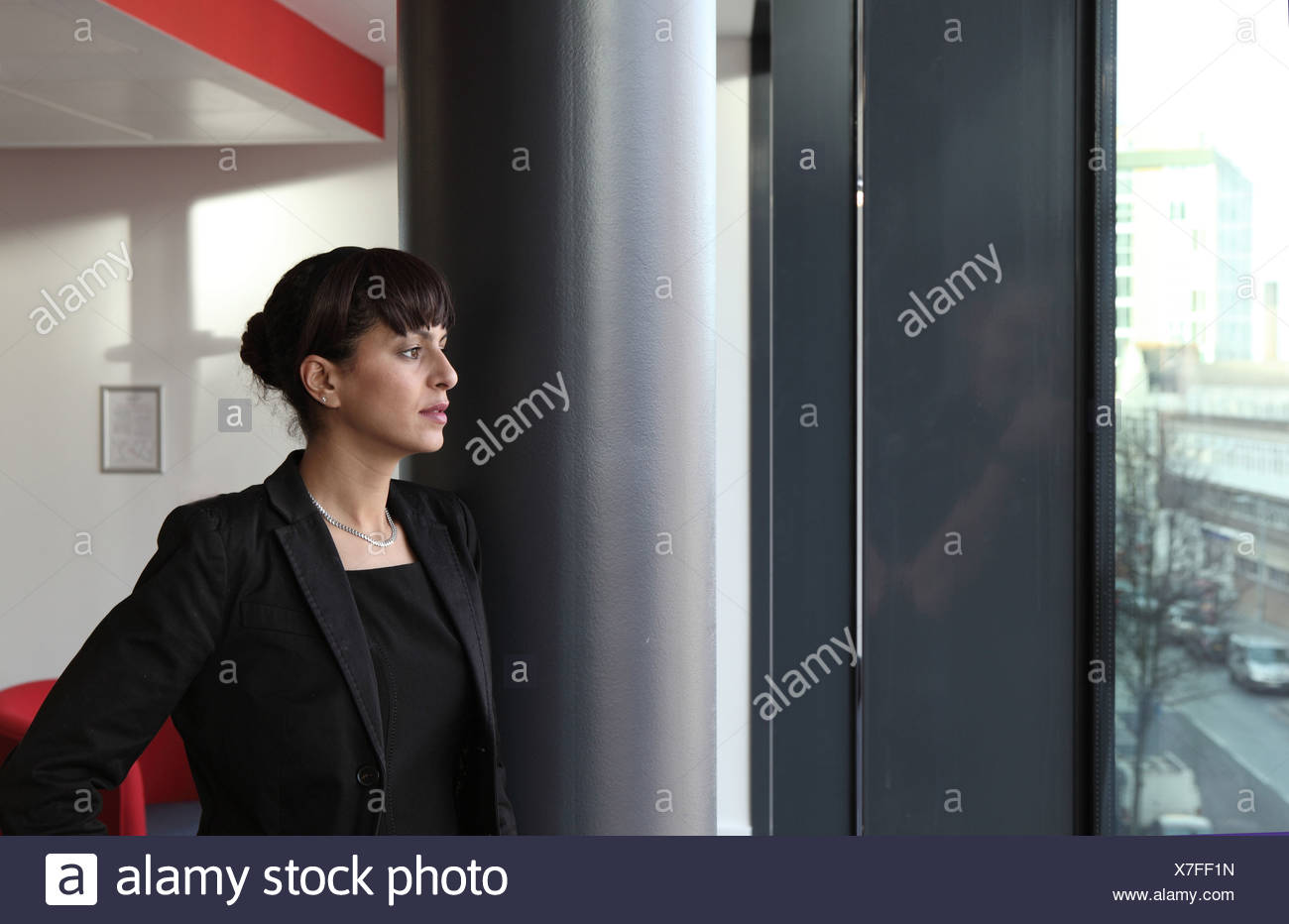Businesswoman looking out office window - Stock Image