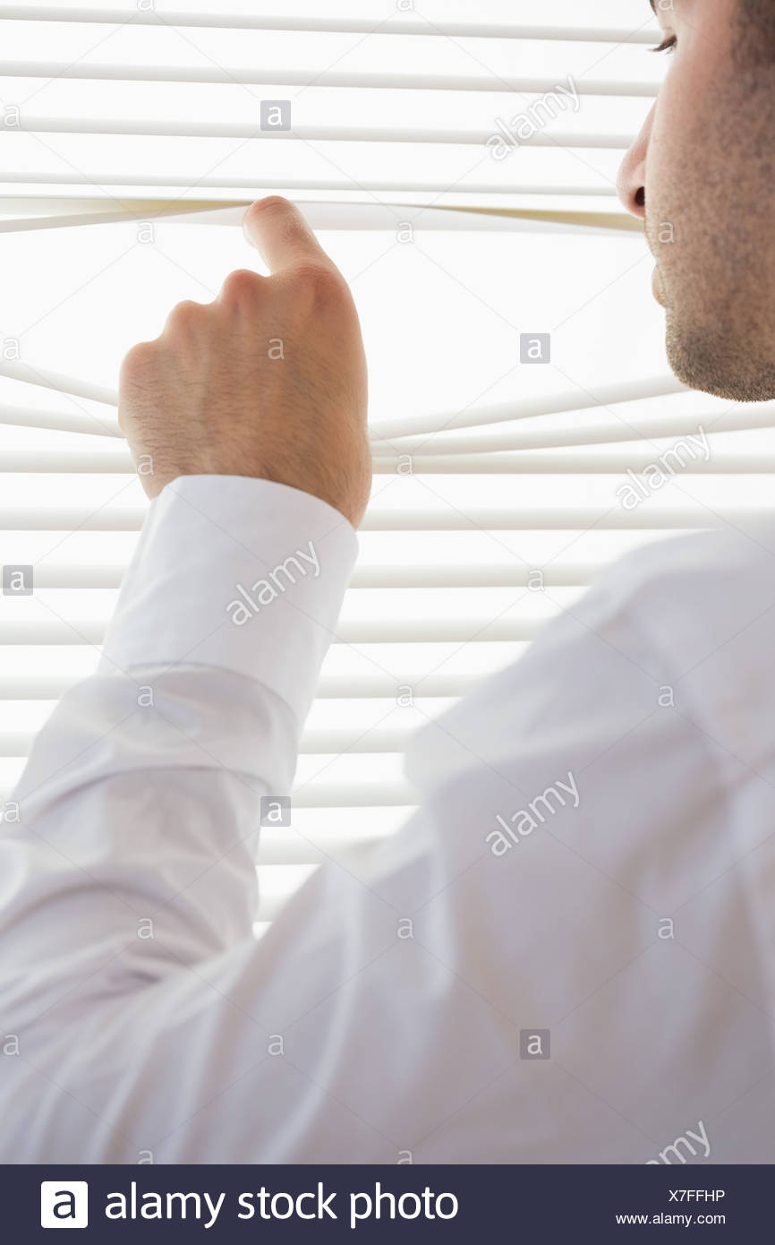 Attractive businessman spying through roller blind - Stock Image