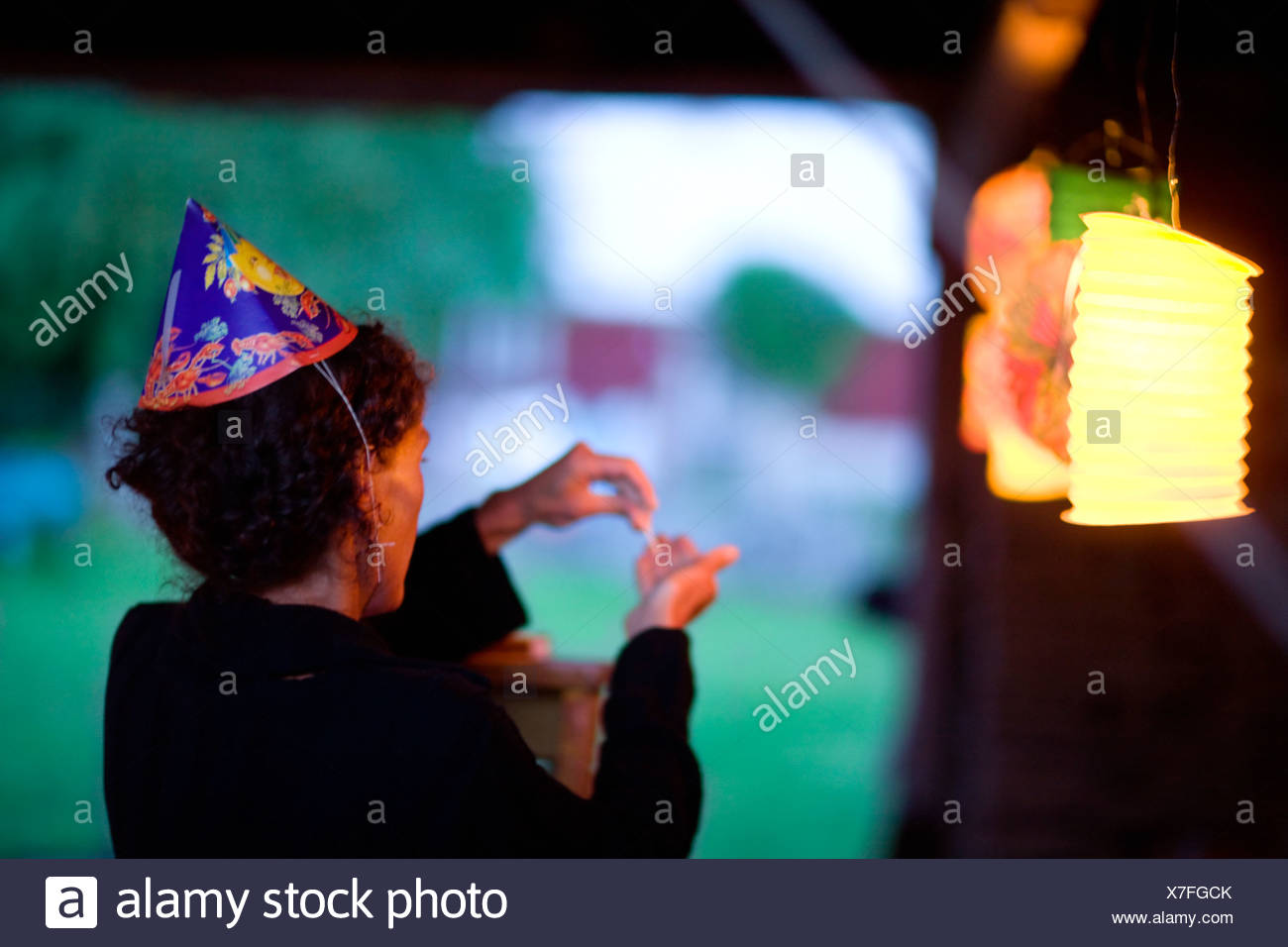 Woman wearing party hat standing by illuminated lantern - Stock Image