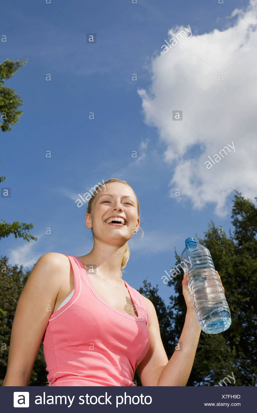 Germany, Berlin, Young woman holding water bottle, laughing, portrait - Stock Image