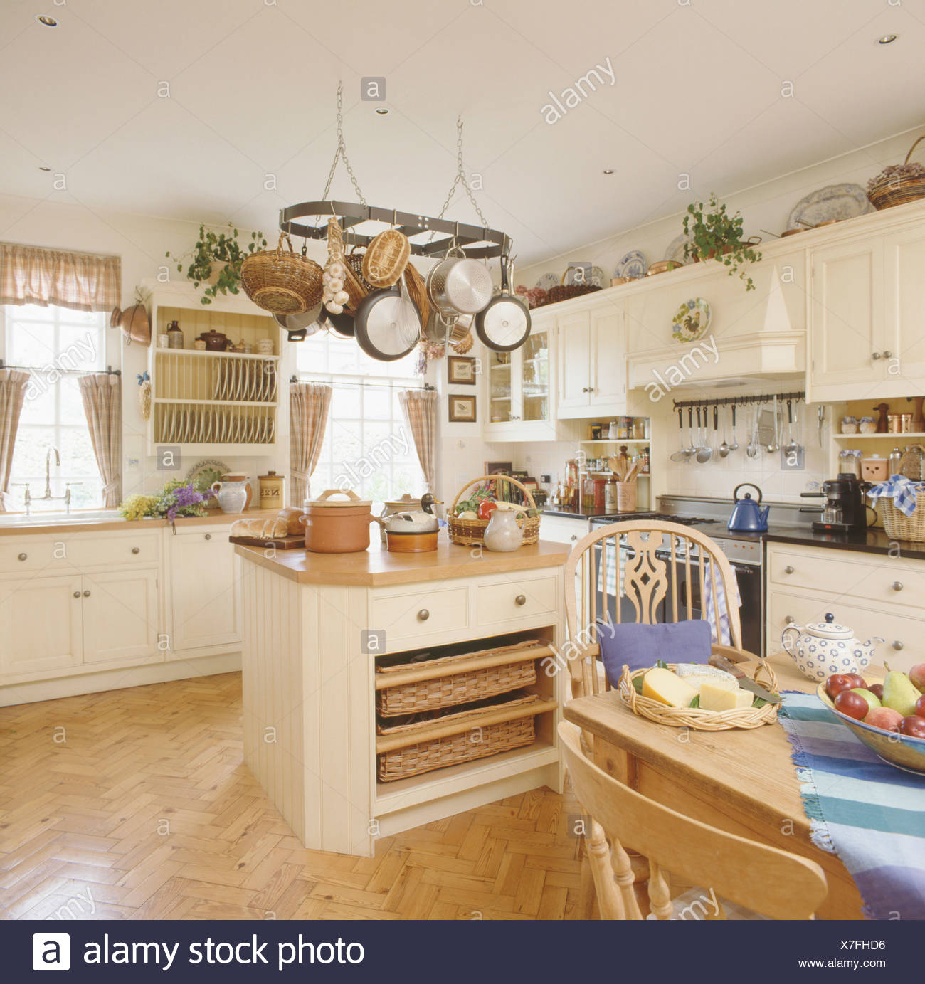 Pans On Rack Above Island Unit With Storage Baskets On Shelves In Cream Kitchen With Parquet Flooring Stock Photo Alamy