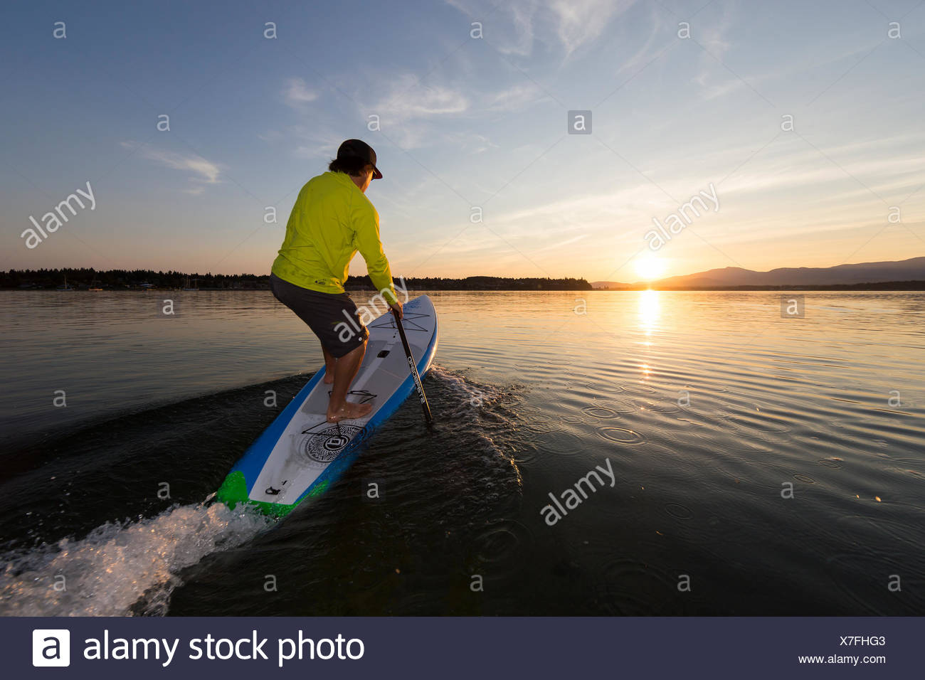 A Stand up paddleboarder launches into the sunset waters off of Goose Spit Regional Park.  Comox, The Comox Valley, Vancouver Island - Stock Image