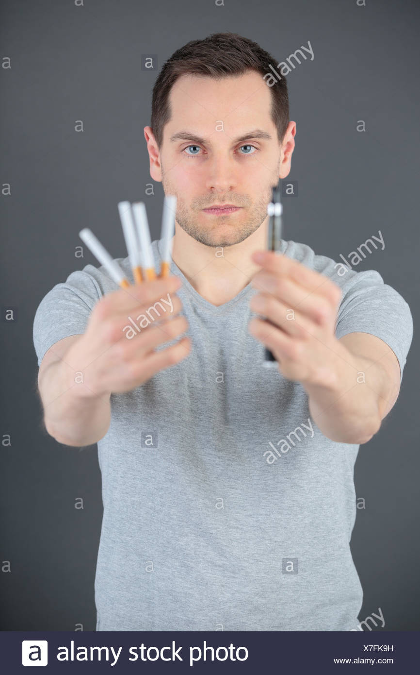man comparing classic tobacco cigarette and electronic cigarette or vaporizer - Stock Image