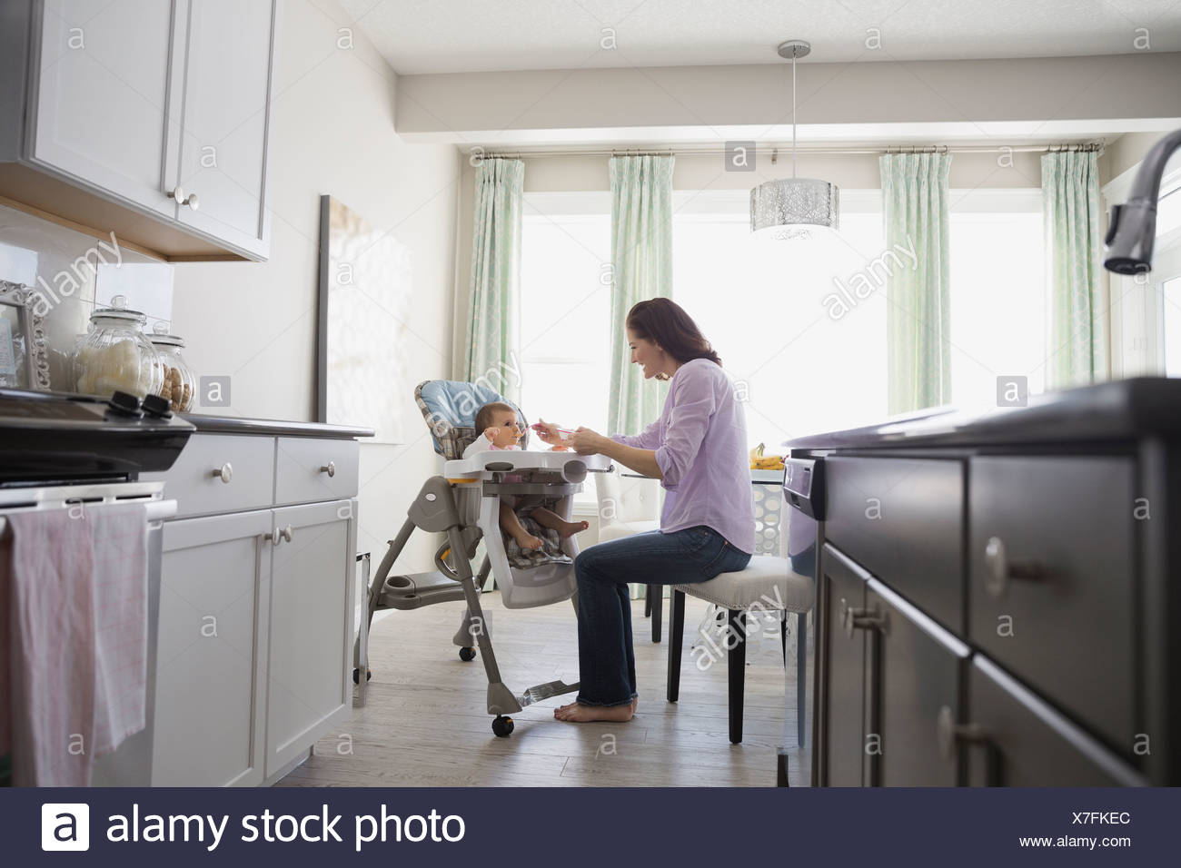 Woman feeding baby girl at home - Stock Image