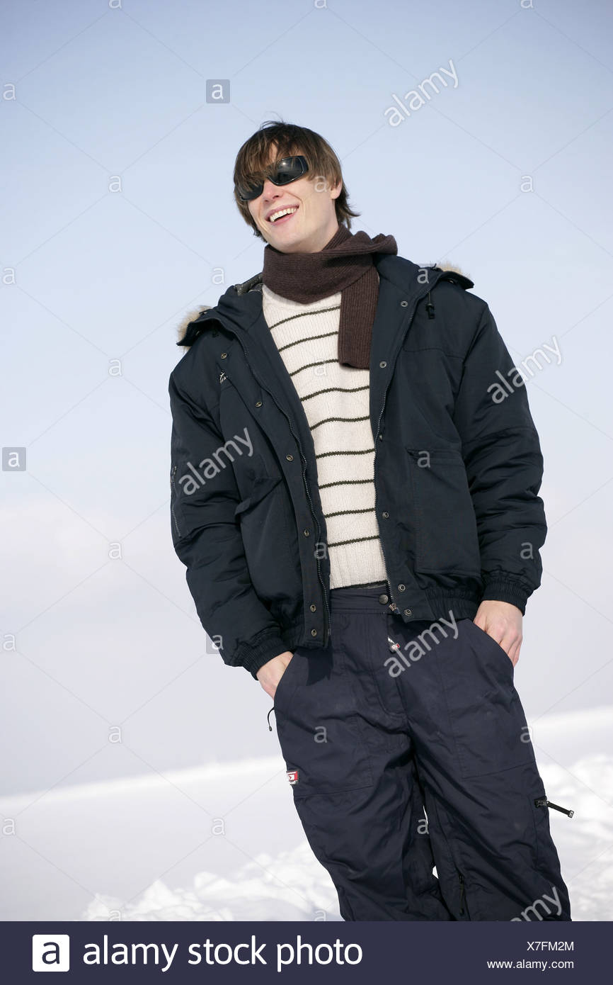 Man young smiles sun glass winter-clothing snow gets along 20-30 years outside look at the side cheerfully jacket season young - Stock Image