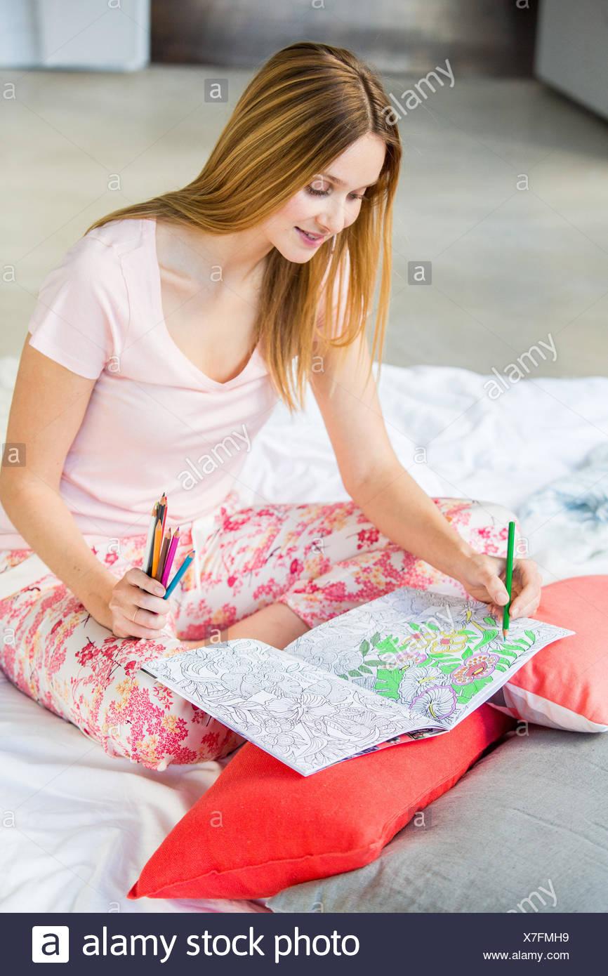 Woman coloring a mandala. - Stock Image
