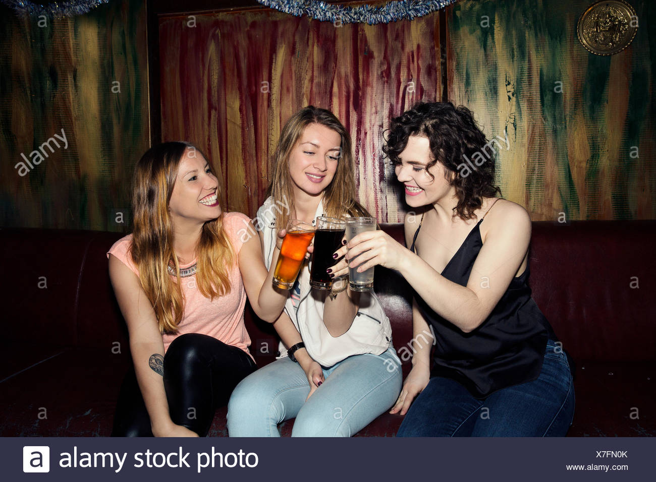 Three adult female friends raising a glass in bar - Stock Image