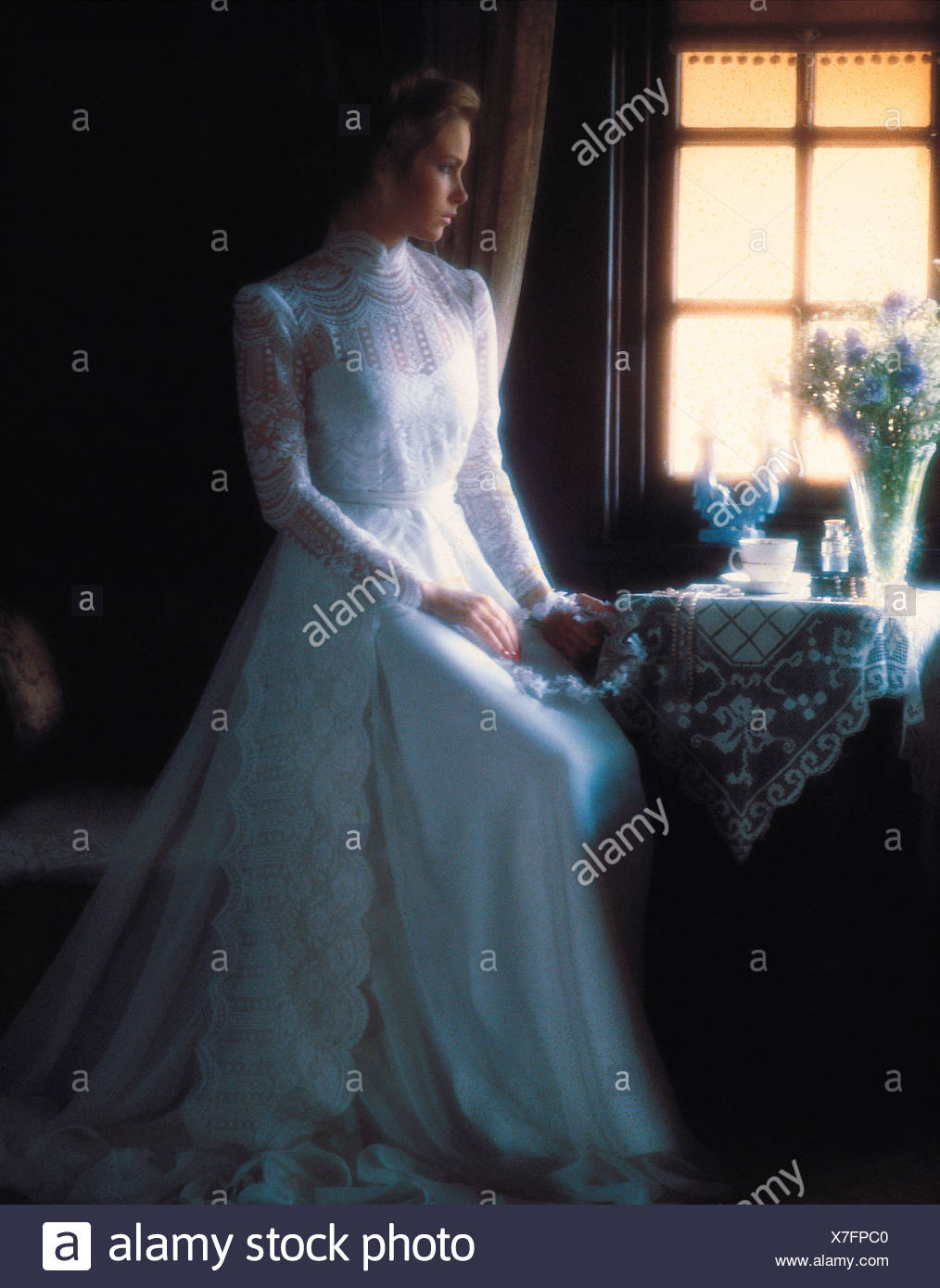 Young woman in long white bridal gown seated by window. Stock Photo