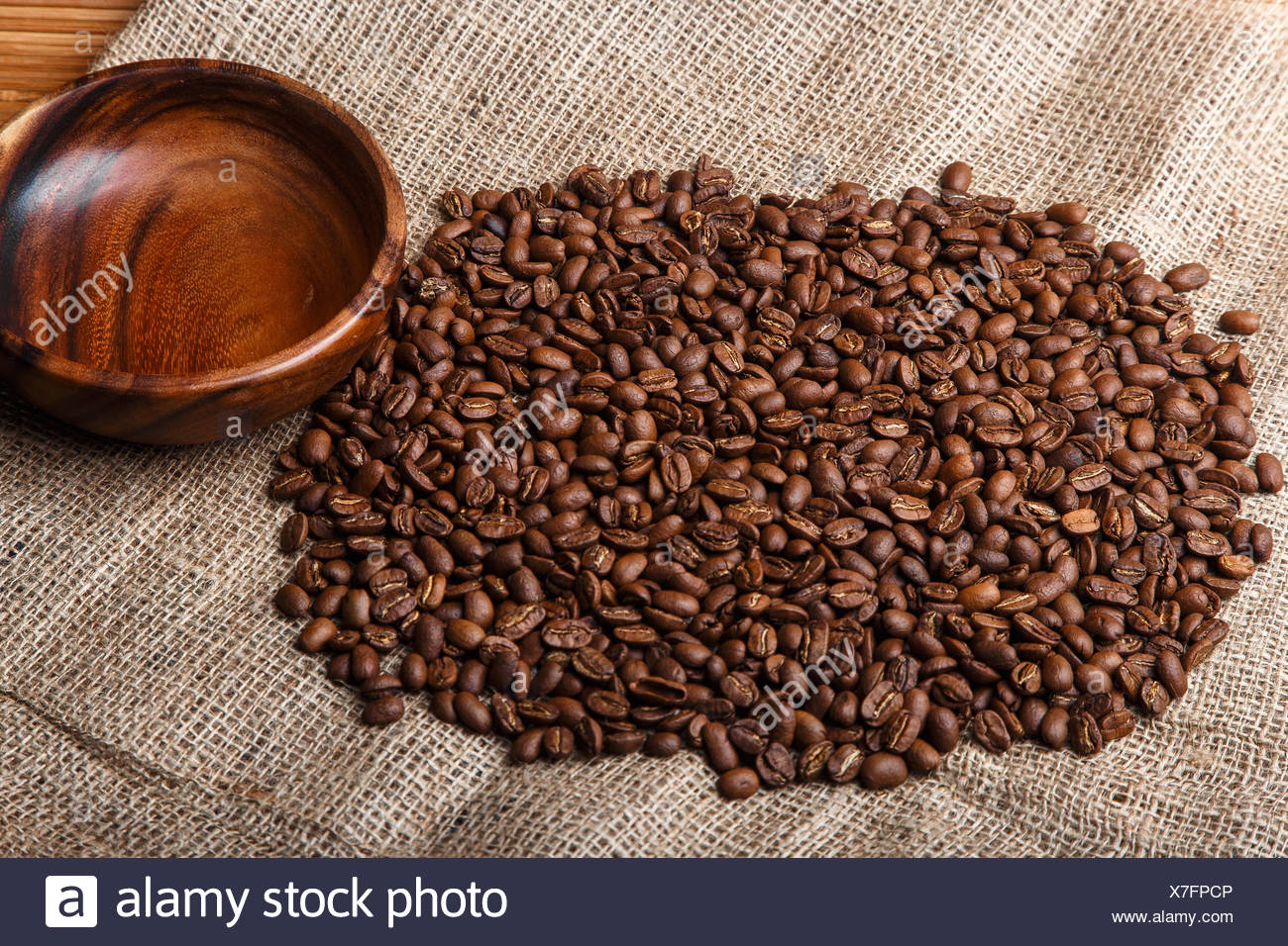Brown coffee beans on the bag with empty wooden di - Stock Image
