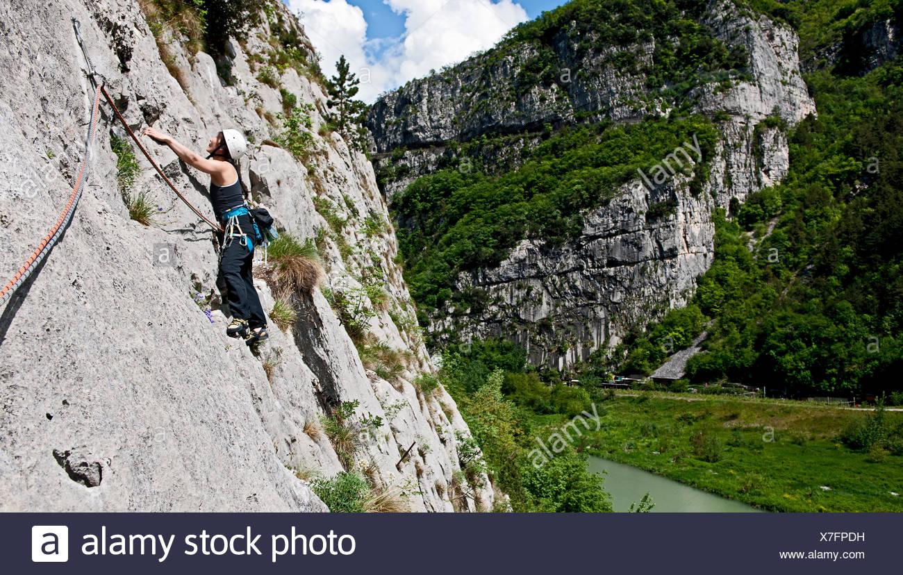 Woman climber traversing on multi pitch route, Amazziona at Piccolo Dain Parete della Centrale, Sarche, Trentino, Italy - Stock Image